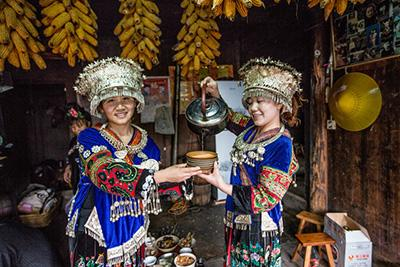 girls pouring tea in Langde Miao Village
