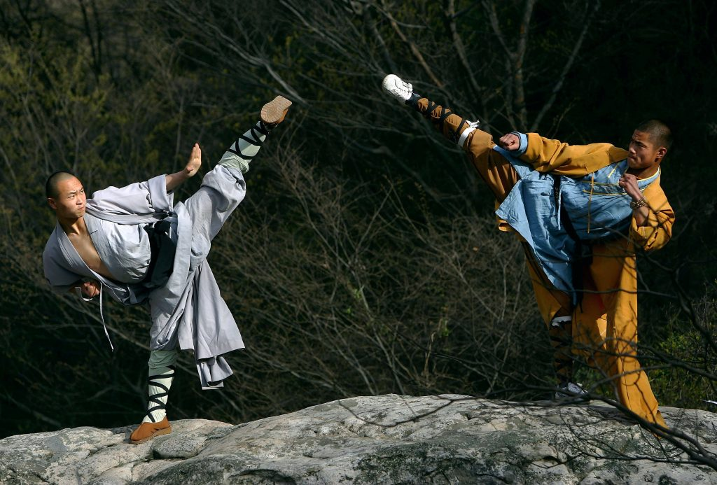 DENGFENG, CHINA - APRIL 12: Warrior monks of the Shaolin Temple display their Kung Fu skills at the Songshan Mountain near the temple April 12, 2005 in Dengfeng, Henan Province, China. Shaolin Temple, built in AD 495 in the period of the Northern and Southern Dynasties (420-581) and located in the Songshan Mountain area, is the birthplace of Shaolin Kung Fu. Shaolin Kung Fu, with its incredible strength, vitality and flexibility, is expecting to be included in the UNESCO intangible heritage list. (Photo by Cancan Chu/Getty Images)